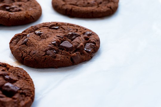 Close up picture of dark chocolate cookies on baking papre