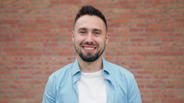 A man with a beard smiling against a brick wall background. Medium shot. Soft focus