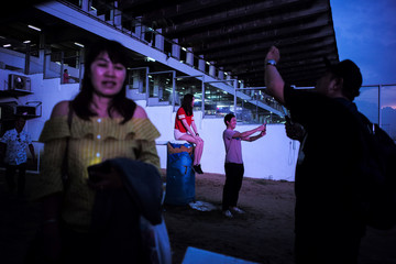 People take selfies after a last horse race at the Nang Leong racecourse in Bangkok