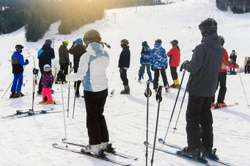 Family skiing on ski resort. Waiting for the piste