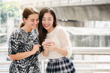 Portrait two beautiful women standing holding smartphones in big city. Find a place to eat And shopping out the salary range. Also search for airfare to use on travel, discounted price by promotion.