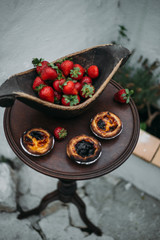 Fresh strawberry and Pastel de nata - traditional Portuguese cake in a old wooden plate on rustic table