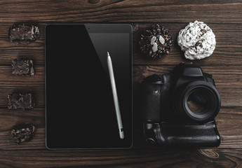 Professional camera and tablet touch computer with pen on wooden table.Top view