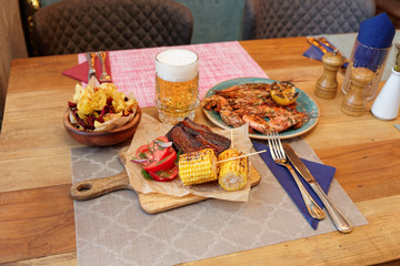 Flame fried meat, corn, potato chips and beer