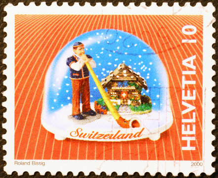 Swiss souvenir with man playing alphorn on postage stamp