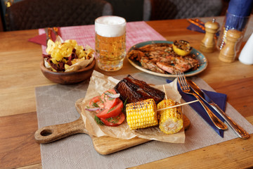 Grilled meat, corn, potato chips and beer