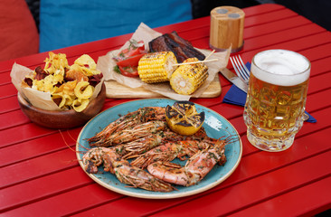 Meat, seafood and potato chips served with beer