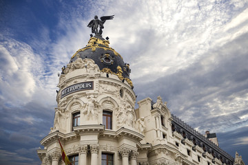 Metropolis - one of the most beautiful buildings in Madrid, Spain with dramatic blue cloudy sky on the background Wall mural
