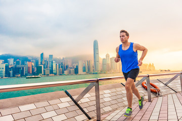 Running man runner in Hong Kong city urban skyline. Caucasian athlete training cardio jogging on the promenade of Victoria Harbor in HongKong, China, in afternoon sunset during summer.