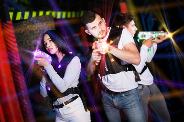 Young people on lasertag in colorful beams