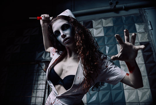 Horror shot: horrible wicked mad nurse (doctor) in bloody uniform killing by syringe. Zombie woman (living dead). Monster from nightmare