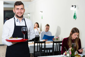Portrait of waiter who is standing with dish in restaurante