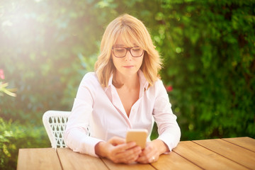 Outdoor portrait of a middle age woman text messaging