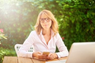 Woman working outside and using global technology. Home office.