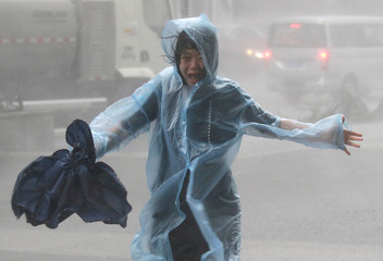 Woman runs in the rainstorm as Typhoon Mangkhut approaches in Shenzhen