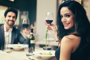 Couple toasting wineglasses in a luxury restaurant, toned image
