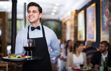 Waiter posing in restaurant