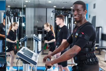 Sporty man training EMS in gym