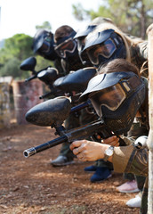 Paintball players aiming with gun in shootout outdoors