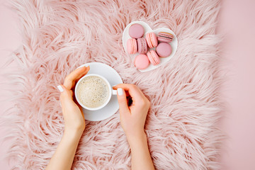Female hands holding a cup of coffee with macaroons on the fluffy fur plaid.  Flat lay, top view