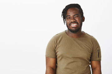 Waist-up shot of positive happy african-american man with beard, winking and smiling broadly with perfect white teeth, feeling joyful while hanging out over gray background with cheerful attitude