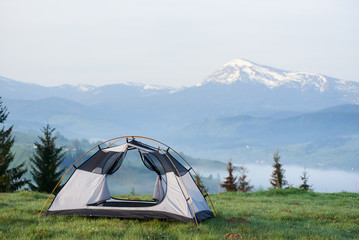 Open empty small tourist tent on grassy hill on background of pine trees and distant mountain range with snowy peaks lit by morning sun. Tourism, camping, recreation and beauty of nature concept.