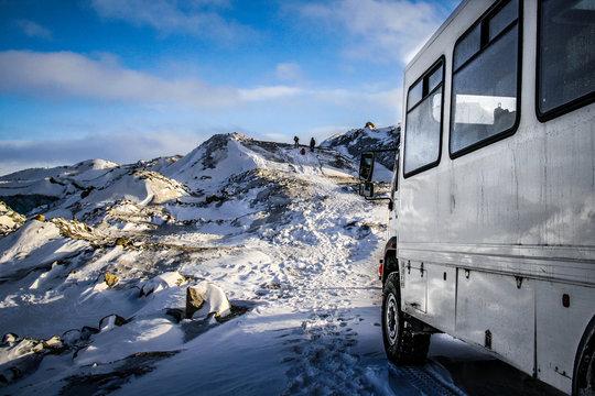 KANGERLUSSUAQ, GREENLAND - Oct 2009: An overland truck waits for tourists as they trek along a snowy ridge towards the inland ice cap near Kangerlussuaq in west Greenland