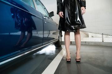 Jambes de femme dans un parking près d'une voiture