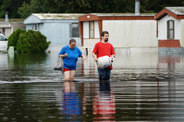 People walk on a flooded street after Hurricane Florence struck Piney Green