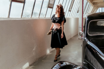 Femme en tenue retro et voiture ancienne regardant à travers la fenêtre