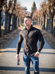 One handsome young man in urban setting in European city walking along street with trees, wearing black jacket and jeans