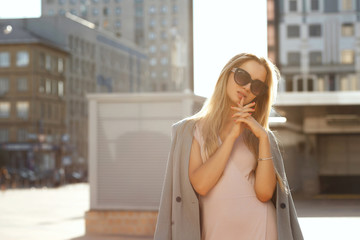 Adorable blonde model wearing trendy dress and grey jacket, posing outdoor in rays of sun. Space for text