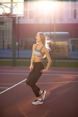 Pleased fitness model in sport clothes with long fluttering hair jumping on a tennis court