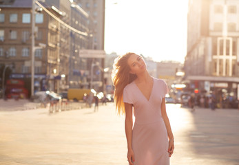 Gorgeous blonde woman posing at the street in a rays of sun. Lifestyle fashion concept. Space for text
