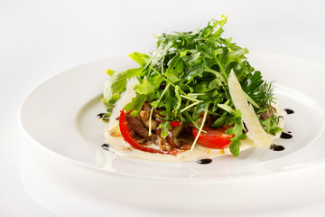 Plate of beef salad served with parmesan, green and tomato isolated at white background.