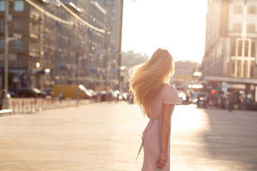 Slender blonde woman with fluttering hair posing at the street in sun beam. Female fashion concept. Space for text