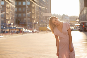Stylish blonde woman with fluttering hair posing at the street in sun beam. Female fashion concept. Space for text