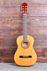 Acoustic guitar on wooden background. Yellow guitar on brown textured background. Classical stringed instrument.