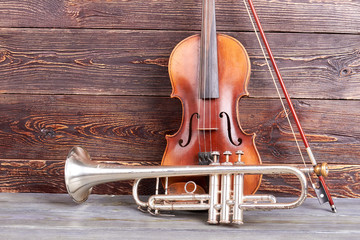 Trumpet and violin on wooden background. Vintage musical instruments on brown wooden surface.
