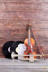 Set of vintage musical instruments. Group of musical instruments including violin, trumpet, vinyl records and sheets of musical notes. Retro musical objects.