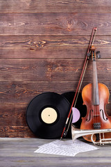 Set of musical instruments and copy space. Vinyl records, violin, trumpet and sheets of musical notes on wooden background.