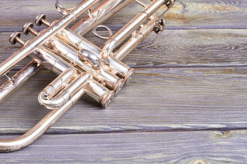 Vintage trumpet and copy space. Old musical instrument on wooden background. Retro jazzy equipment.