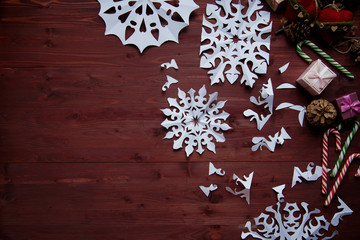 New Year's concept. Snowflakes cut from paper, gifts, scissors on a wooden table