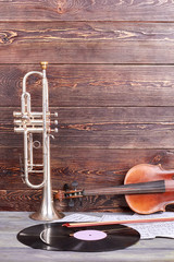 Vintage musical instruments on wooden background. Trumpet, violin, vinyl record and musical notes. Instruments of orchestra.