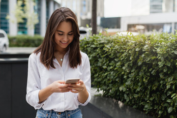 Happy businesswoman using mobile phone near office, beautiful woman browsing phone smiling walking outdoors, female manager texting using modern smartphone. Copy space for text or design