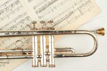Old rusty trumpet and musical notes. Close up vintage trumpet and musical sheets on light background, horizontal image.