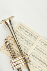 Rusty trumpet on musical notes, top view. Music notes book and trumpet with clipping path. Classical wind instrument.