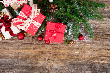 Christmas gift giving concept - christmas presents in red and white boxes on wooden table, flat lay scene with copy space