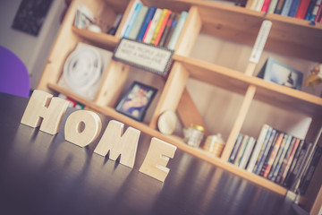 Zu Hause: HOME-Buchstaben auf schwarzem Tisch, Bücherregal im Hintergrund, Unschärfe