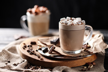 Composition with two glass of cappuccino topped with marshmallow and served with coffee beans and chocolate on wooden chopping board over black background